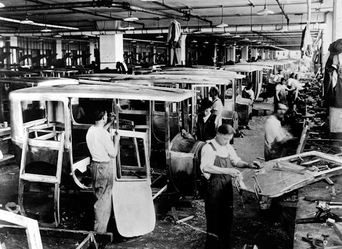 FILE - This 1920s photo shows employees working in the Packard Motor Car Co. in Detroit. (AP Photo/File)