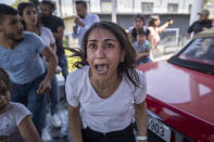 A Syrian woman screams for help for her husband who was injured by stone throwing by members of the Lebanese Forces group, who attacked buses carrying Syrians traveling to vote in the town of Zouk Mosbeh, north of Beirut, Lebanon, Thursday, May 20, 2021. Mobs of angry Lebanese men attacked vehicles carrying Syrians expatriates and those who fled the war heading to the Syrian embassy in Beirut on Thursday, protesting against what they said was an organized vote for President Bashar Assad. (AP Photo/Hassan Ammar)