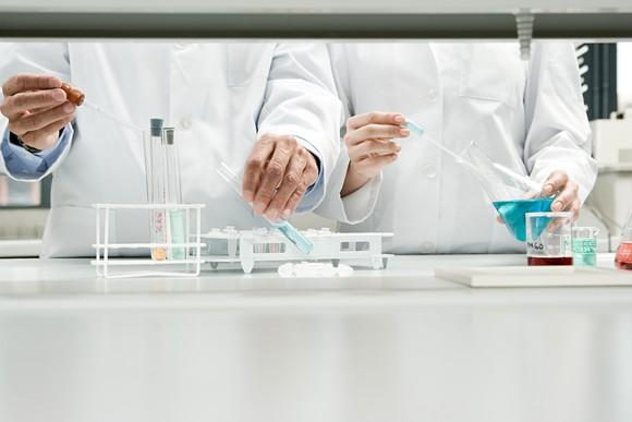 Two scientists standing side by side in lab with test tubes and beakers in front of them