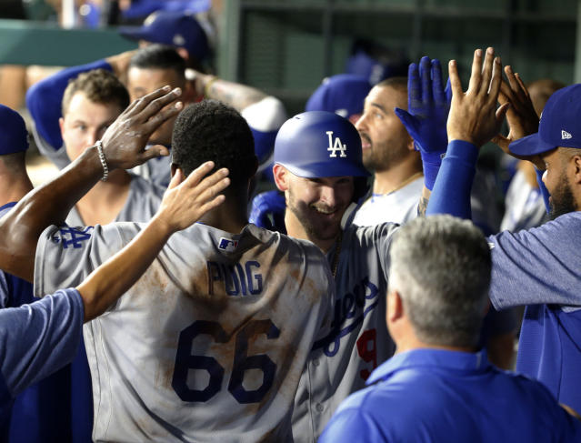 Los Angeles Dodgers' Yasiel Puig (66) congratulates Yasmani Grandal (9) after Grandal's solo home run against the Texas Rangers during the eighth inning of a baseball game Wednesday, Aug. 29, 2018, in Arlington, Texas. (AP Photo/Michael Ainsworth)