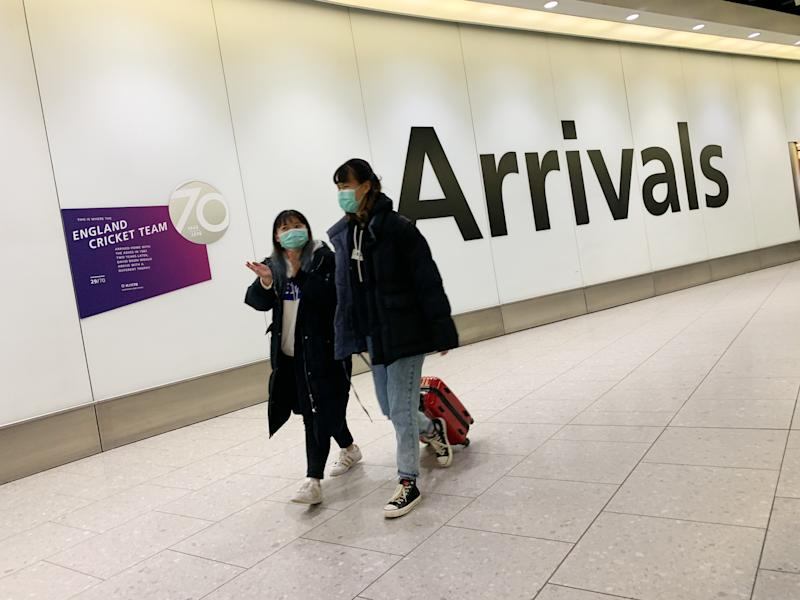 People arriving at Heathrow Airport, London wear face masks as the outbreak of Coronavirus spreads in China (Picture: SWNS)