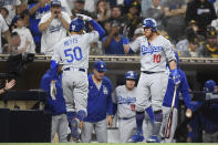 Los Angeles Dodgers' Mookie Betts (50) is congratulated by Justin Turner (10) after hitting a solo home run during the third inning of a baseball game against the San Diego Padres, Monday, June 21, 2021, in San Diego. (AP Photo/Denis Poroy)