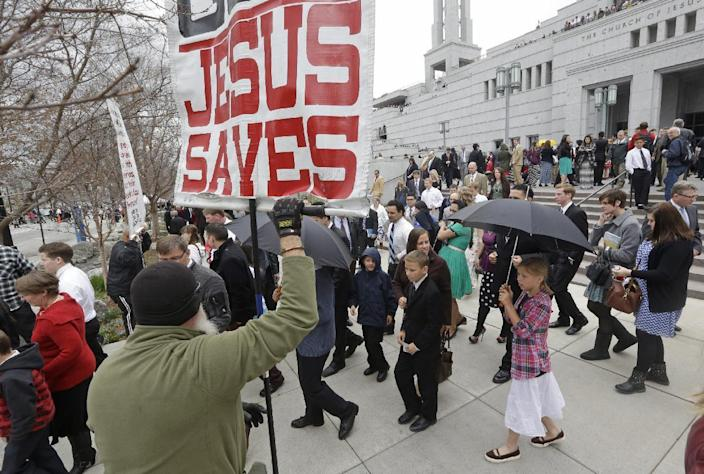 People walk pass a unidentified protester on their way from the Conference Center during opening session of the two-day Mormon church conference Saturday, April 5, 2014, in Salt Lake City. More than 100,000 Latter-day Saints are expected in Salt Lake City this weekend for the church's biannual general conference. Leaders of The Church of Jesus Christ of Latter-day Saints give carefully crafted speeches aimed at providing members with guidance and inspiration in five sessions that span Saturday and Sunday. They also make announcements about church statistics, new temples or initiatives. In addition to those filling up the 21,000-seat conference center during the sessions, thousands more listen or watch around the world in 95 languages on television, radio, satellite and Internet broadcasts. (AP Photo/Rick Bowmer)