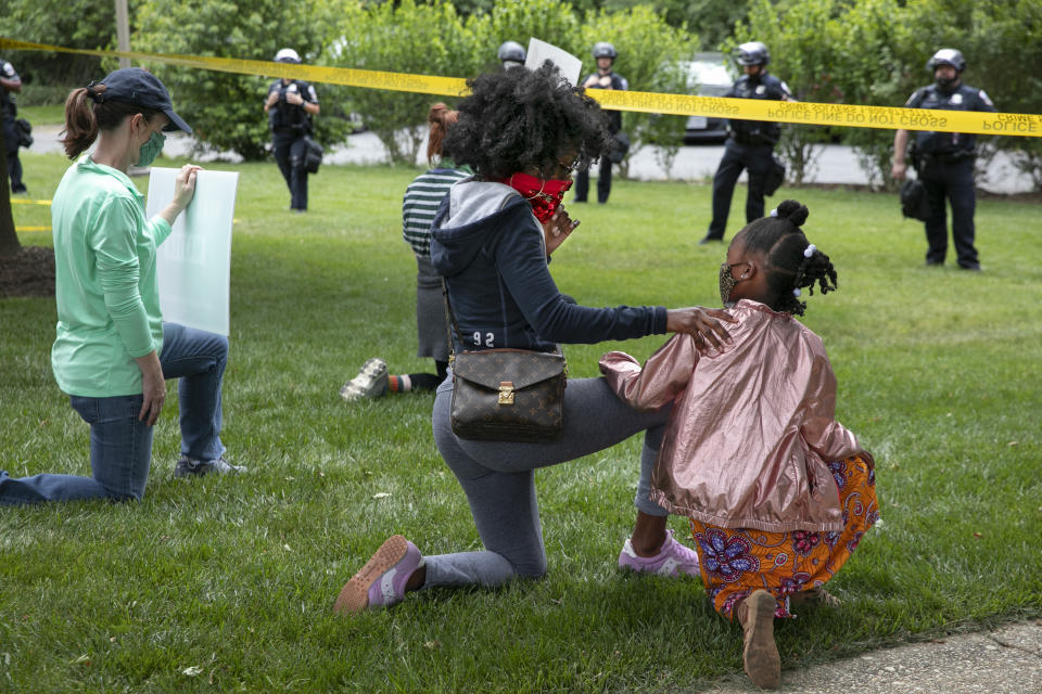 """Ericka Ward-Audena, of Washington, puts her hand on her daughter Elle Ward-Audena, 7, as they take a knee in front of a police line during a protest of President Donald Trump's visit to the Saint John Paul II National Shrine, Tuesday, June 2, 2020, in Washington. """"I wanted my daughter to see the protests, it's really important. I've gotten a million questions from her because of it,"""" says Ward-Audena, """"I think the most egregious statement was 'when they start looting, we start shooting.' That crossed a line for me."""" Protests continue over the death of George Floyd, who died after being restrained by Minneapolis police officers. (AP Photo/Jacquelyn Martin)"""