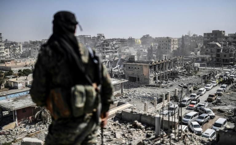 A fighter from the US-backed Syrian Democratic Forces stands guard on a rooftop in Raqa after the Syrian city's recapture from the Islamic State group