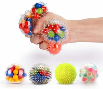 four stress balls and one hand squeezing a colorful stress ball above the other ones