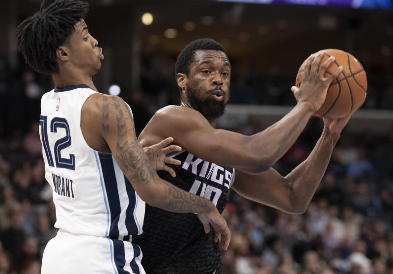 Sacramento Kings forward Harrison Barnes (40) looks to pass while defended by Memphis Grizzlies guard Ja Morant (12) during the first half of an NBA basketball game Friday, Feb. 28, 2020, in Memphis, Tenn. (AP Photo/Nikki Boertman)