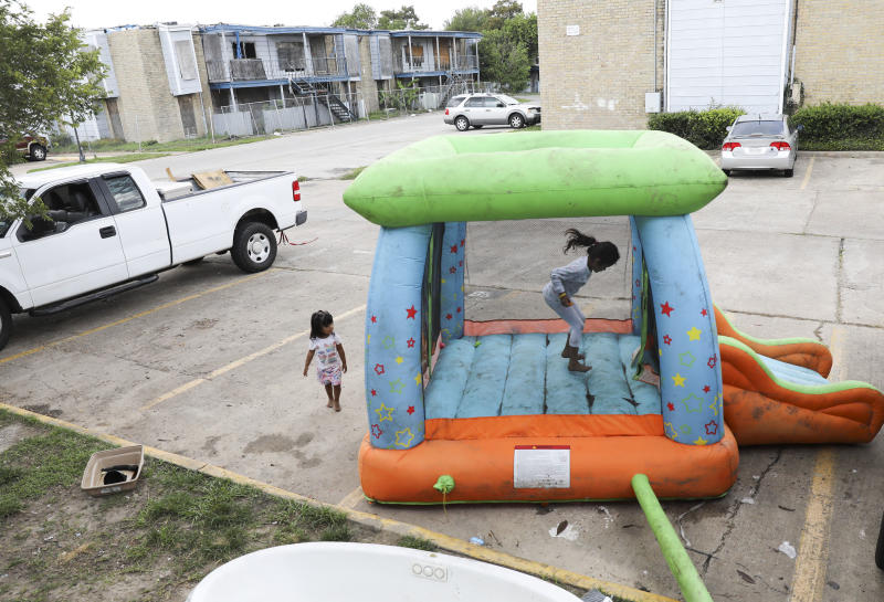 Monica Cruz, 7, jumps in an inflatable bouncy house as her neighbor Ashley Guerrero Monterrosa, 2, walks in the parking lot as residents clean up from Tropical Storm Harvey at Rockport Apartments.