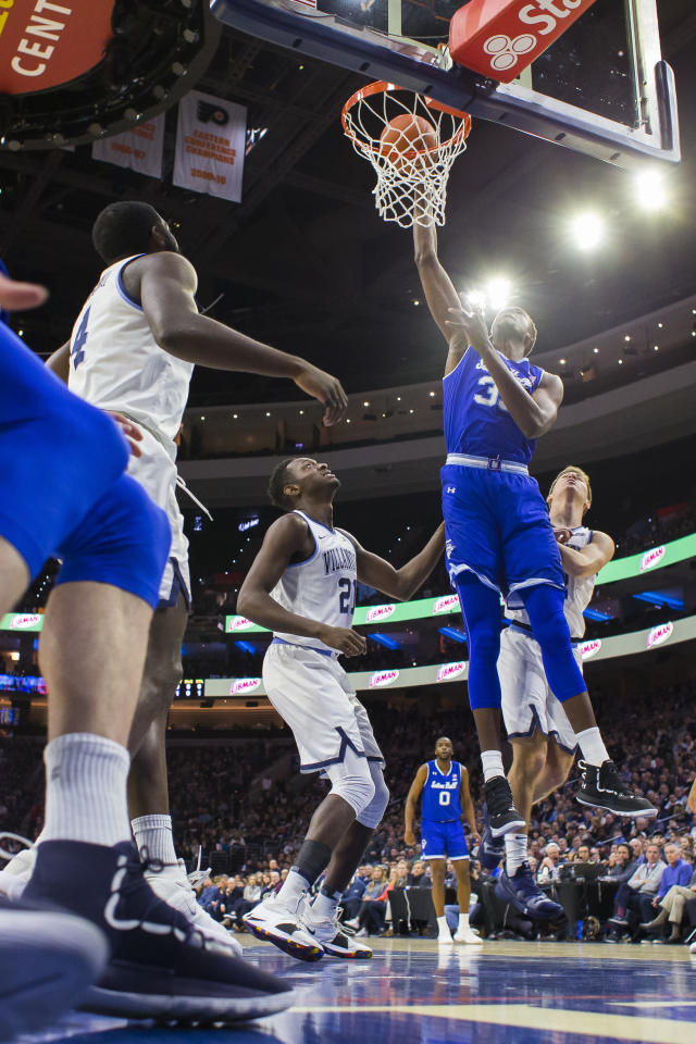 Seton Hall's Romaro Gill, center, dunks as Villanova's Dhamir Cosby-Roundtree, left, and Collin Gillespie, right, defend during the first half of an NCAA college basketball game, Sunday, Jan. 27, 2019, in Philadelphia. (AP Photo/Chris Szagola)