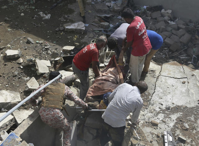 Volunteers carry the dead body of a plane crash victim at the site of a crash in Karachi, Pakistan, Friday, May 22, 2020. An aviation official says a passenger plane belonging to state-run Pakistan International Airlines carrying more than 100 passengers and crew has crashed near the southern port city of Karachi. There were no immediate reports on the number of casualties. (AP Photo/Fareed Khan)