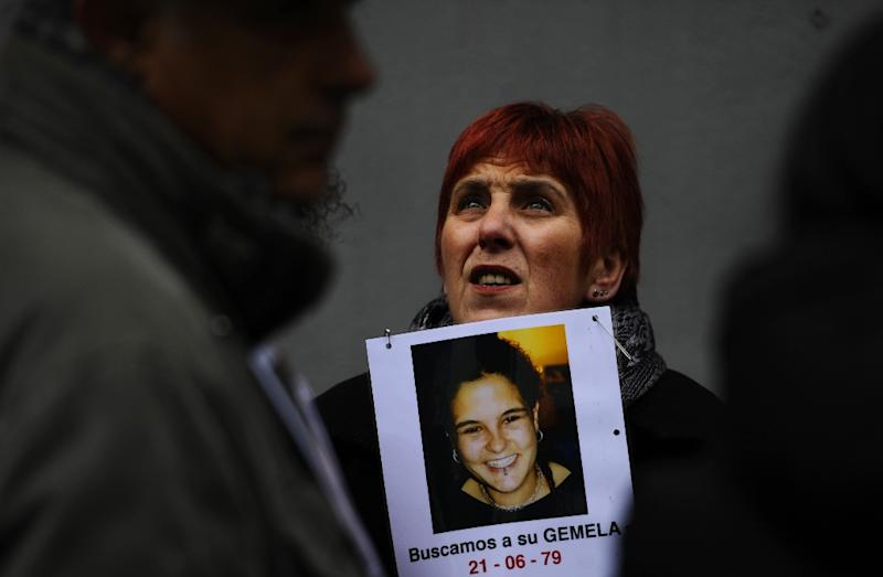 """A file picture taken on January 27, 2012 shows a woman holding a poster displaying a picture of a young girl and reading """"We are looking for her twin sister"""" during a demonstration against baby trafficking in Madrid (AFP Photo/Pierre-Philippe Marcou)"""