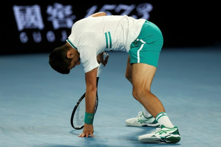 Novak Djokovic is doubled up in pain after stretching for a shot against Milos Raonic