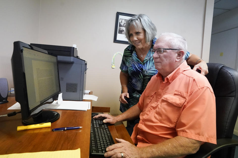 Roger West, right, columnist of the Westside Journal in northeast Florida, looks over news copy with his wife Dawn, owner and publisher, in the newspaper office Tuesday, Aug. 10, 2021, in Callahan, Fla. Outspoken as he had been in opposing COVID-19 vaccines he reconsidered after the virus returned with a deadly vengeance in mid-July. (AP Photo/John Raoux)