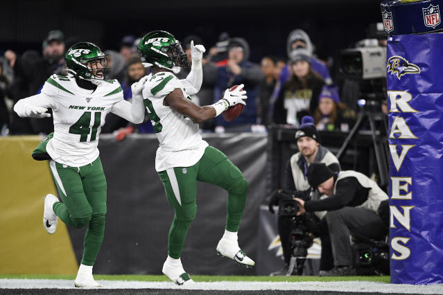 New York Jets linebacker B.J. Bello (49) reacts while returning a Baltimore Ravens blocked punt for a touchdown during the second half of an NFL football game, Thursday, Dec. 12, 2019, in Baltimore. Jets defensive back Matthias Farley (41) joins in the celebration. (AP Photo/Nick Wass)