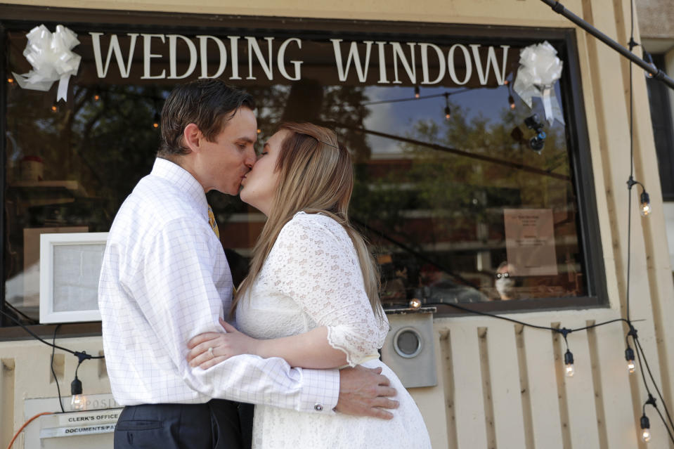 Justin and Joanne Waters kiss after they were married in a walk up and drive-thru wedding ceremony at the Family and Civil courthouse in Gainesville, Fla. Thursday, May 14, 2020. (AP Photo/John Raoux)
