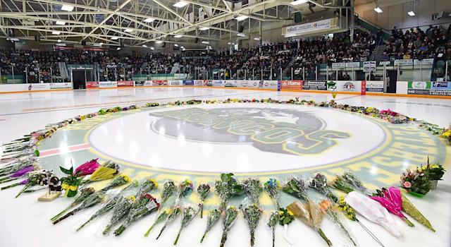 Flowers lie at centre ice as people gather for a vigil at the Elgar Petersen Arena. (Jonathan Hayward/CP)