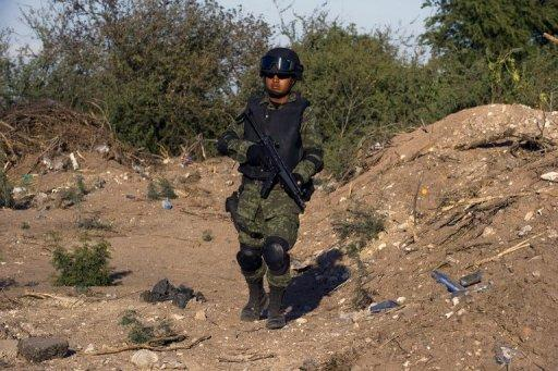 A Mexican soldier stands guard at a checkpoint on the road that links Navolato and Los Mochis, in Sinaloa State, Mexico