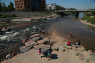 People cool off in the water at the confluence of the South Platte River and Cherry Creek in Denver, Colorado on June 14, 2021. By mid-afternoon, the temperature hit 96 degrees as part of the heat wave sweeping across the western U.S. (AP Photo/Brittany Peterson)