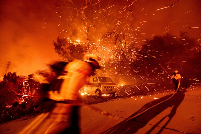 Firefighters battling the Bond Fire haul a hose while working to save a home in the Silverado community in Orange County, Calif., on Thursday, Dec. 3, 2020.