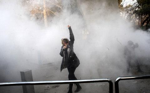 An Iranian woman raises her fist amid the smoke of tear gas at the University of Tehran during a protest driven by anger over economic problems, in the capital Tehran on December 30, 2017 - Credit: AFP PHOTO / STRSTR/AFP/Getty Images