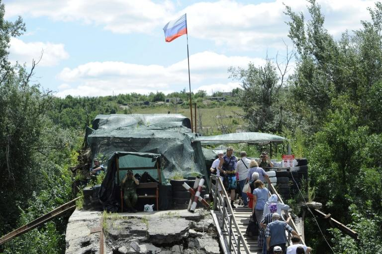 At Stanytsya Luganska, about 11,000 people cross between Ukrainian territory and the Lugansk People's Republic (LPR) every day via a bridge partially destroyed in 2015 (AFP Photo/Evgeniya MAKSYMOVA)