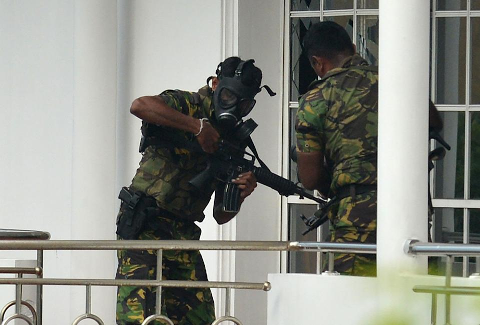 Sri Lankan Special Task Forcepersonnel in gas masks are pictured outside a house during a raid after a suicide blast had killed police searching the property in the Orugodawatta area of the capital Colombo on Sunday. Source: Getty Images