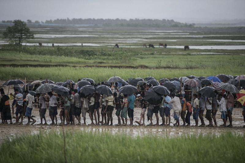 A Rohingya Muslim refugee takes shelter from the rain at the registration center in Teknaf in Bangladesh's Ukhia district on October 6, 2017