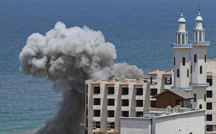 Smoke billows from a building by the sea.
