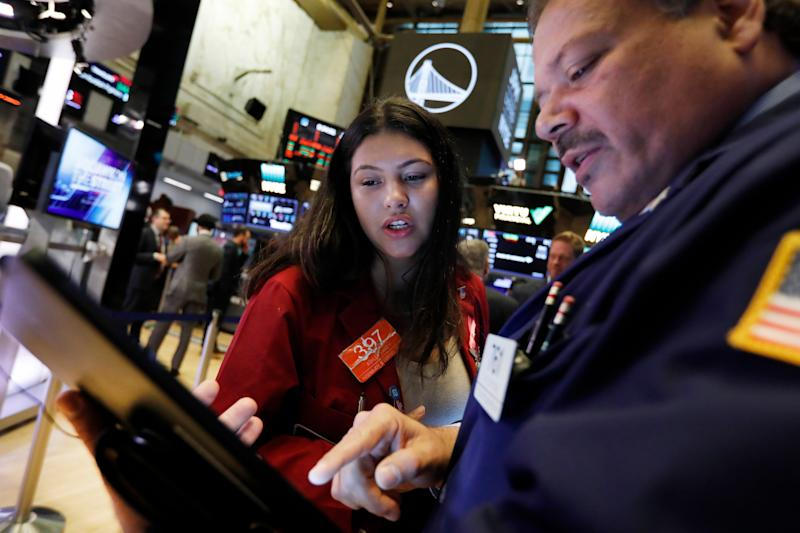 Traders Ashley Lara and John Santiago confer as they work on the floor of the New York Stock Exchange on Oct. 7, 2019. Stocks surged on Wall Street Friday on optimism about U.S.-China trade talks.