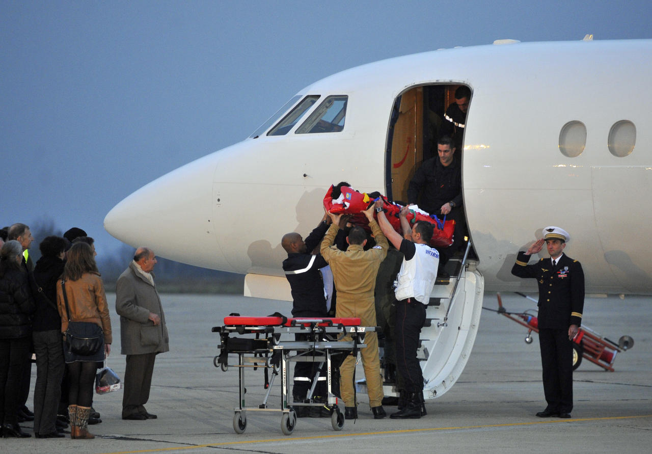 Firefighters and medics carry French wounded journalist Edith Bouvier out of the plane carrying her and French photographer, William Daniels, after they landed at the Villacoublay military airport outside Paris, Friday, March 2, 2012. Two French journalists who were smuggled out of Syria have arrived in France. Edith Bouvier, who was injured, and William Daniels were caught up in a Syrian government siege of a rebel-held neighborhood in the city of Homs.(AP Photo/Zacharie Scheurer)