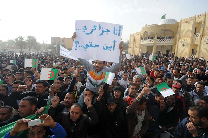 """In this photo dated March 14, 2013, a demonstrator holds a sign reading """"I am Algerian, where are my rights?"""" during a protest by thousands of young unemployed men in Algeria's southern city of Ouargla. Protests by the unemployed in southern Algeria are raising the specter of rising unrest in the country's sensitive oil regions, and are increasingly attracting the attention of al-Qaida. (AP Photo/Nabil Zahani)"""