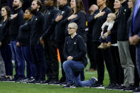 NEW ORLEANS, LOUISIANA - JANUARY 13: A teacher from the Extra Yard for Teachers charity kneels during the National Anthem prior to the Clemson v LSU game in the College Football Playoff National Championship game at Mercedes Benz Superdome on January 13, 2020 in New Orleans, Louisiana. (Photo by Kevin C. Cox/Getty Images)