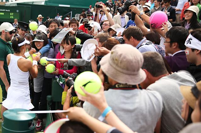 LONDON, ENGLAND - JUNE 27: Kimiko Date-Krumm of Japan signs autographs for fans following her victory in the Ladies' Singles second round match against Alexandra Cadantu of Romania on day four of the Wimbledon Lawn Tennis Championships at the All England Lawn Tennis and Croquet Club on June 27, 2013 in London, England. (Photo by Clive Brunskill/Getty Images)