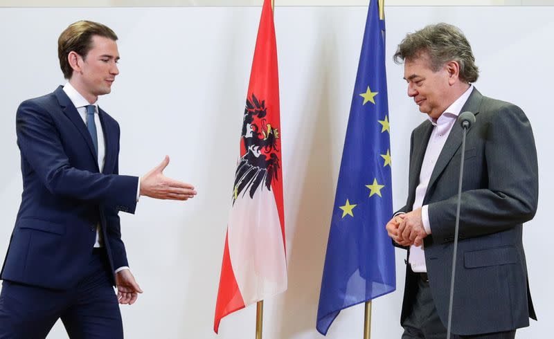 Head of People's Party (OeVP) Sebastian Kurz reaches out to shake hands with Leader of Austria's Green Party Werner Kogler afterdelivering astatementin Vienna