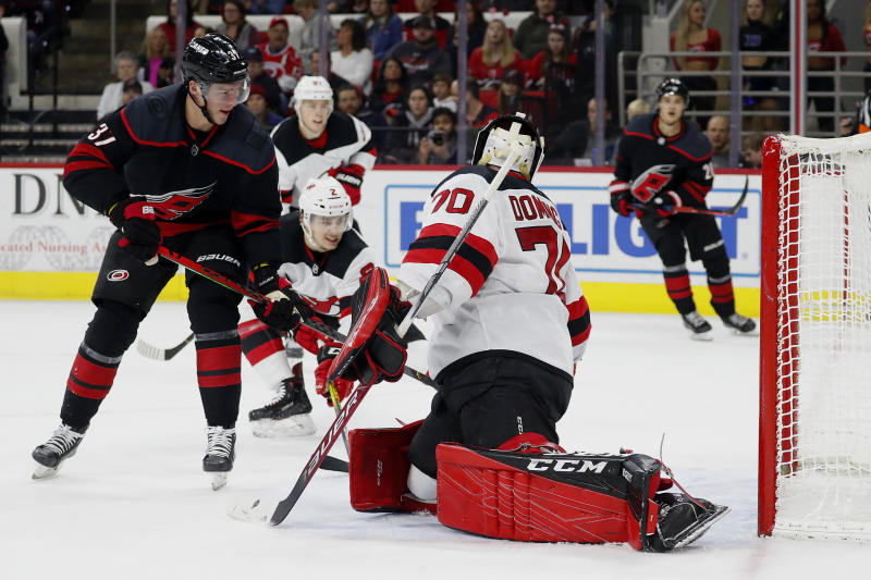Carolina Hurricanes' Andrei Svechnikov (37), of Russia, deflects the puck past New Jersey Devils goaltender Louis Domingue (70) during the second period of an NHL hockey game in Raleigh, N.C., Friday, Feb. 14, 2020. (AP Photo/Karl B DeBlaker)
