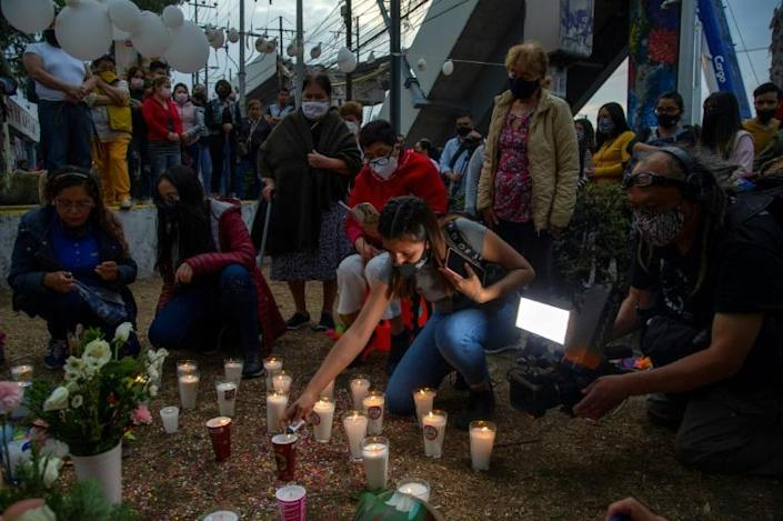 People light candles and place flowers at the site of a Mexico City metro rail accident that left 26 dead and sparked calls for justice
