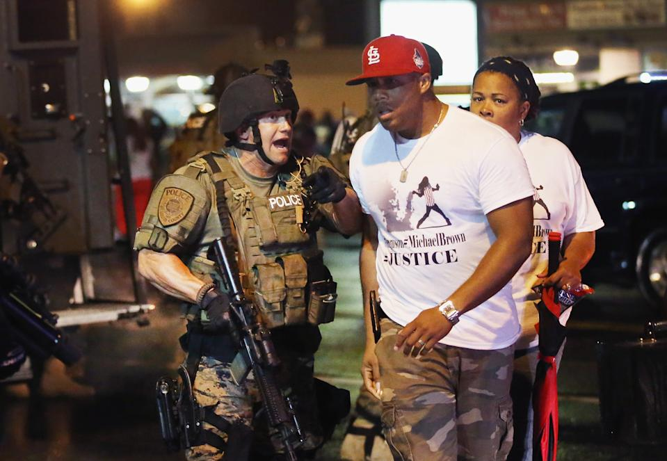 FERGUSON, MO - AUGUST 15:  Police confront demonstrators during a protest over the shooting of Michael Brown on August 15, 2014 in Ferguson, Missouri.  County police shot pepper spray, smoke, gas and flash grenades at protestors before retreating. Several businesses were looted as county police watched from their armored personnel carriers (APC) parked nearby. Violent outbreaks have taken place in Ferguson since the shooting death of Brown by a Ferguson police officer on August 9.  (Photo by Scott Olson/Getty Images)