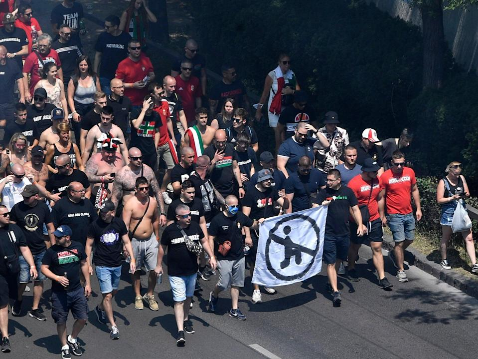 Hungarian fans march with an anti-kneeling banner towards the Puskas Arena in Budapest. (AP)