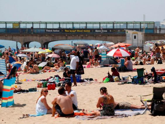 (Sunbathers enjoy the sunny weather on Boscombe beach (ADRIAN DENNIS/AFP via Getty Images)