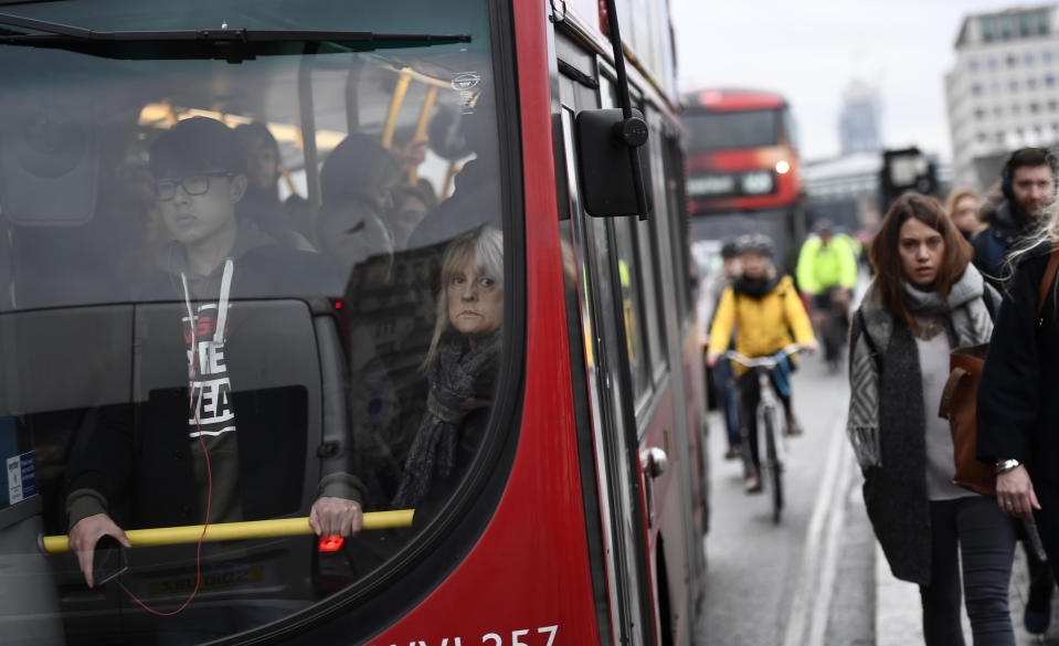 Commuters stand on a packed bus as others walk accross Waterloo Bridge during a strike on the Underground by members of two unions in protest at ticket office closures and reduced staffing levels, in London, Britain January 9, 2017. REUTERS/Dylan Martinez