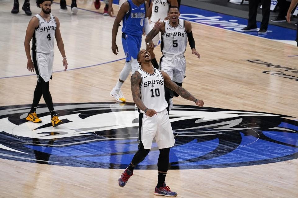 San Antonio Spurs forward DeMar DeRozan, celebrates after sinking a basket in the final second of the second half of an NBA basketball game against the Dallas Mavericks in Dallas, Sunday, April 11, 2021. Spurs' Derrick White (4) and Dejounte Murray (5) look on as DeRozan celebrates. (AP Photo/Tony Gutierrez)
