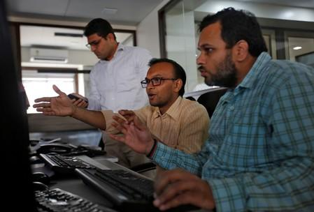 Brokers react while trading during the presentation of the federal budget at a stock brokerage firm in Mumbai