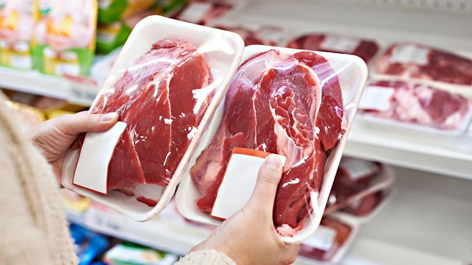 Buyer hands with beef meat packages at the grocery store.