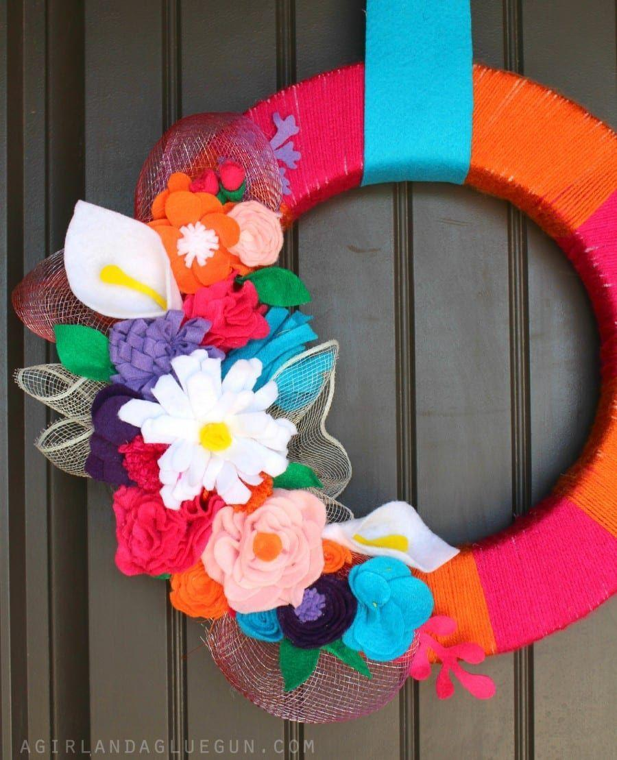 """<p>Now that winter has come to a close, it's time to bust out the color. This Easter wreath is no exception, with its fabric flowers, flamboyant yarn, and ombré-hued mesh. </p><p><strong>Get the tutorial at <a href=""""https://www.agirlandagluegun.com/2015/03/felt-flower-wreath-from-floracraft.html"""" rel=""""nofollow noopener"""" target=""""_blank"""" data-ylk=""""slk:A Girl and a Glue Gun"""" class=""""link rapid-noclick-resp"""">A Girl and a Glue Gun</a>.</strong></p><p><a class=""""link rapid-noclick-resp"""" href=""""https://go.redirectingat.com?id=74968X1596630&url=https%3A%2F%2Fwww.walmart.com%2Fip%2FLion-Brand-DIYarn-Acrylic-Yarn-Hot-Pink%2F172740772&sref=https%3A%2F%2Fwww.thepioneerwoman.com%2Fhome-lifestyle%2Fcrafts-diy%2Fg35698457%2Fdiy-easter-wreath-ideas%2F"""" rel=""""nofollow noopener"""" target=""""_blank"""" data-ylk=""""slk:SHOP YARN"""">SHOP YARN</a></p>"""