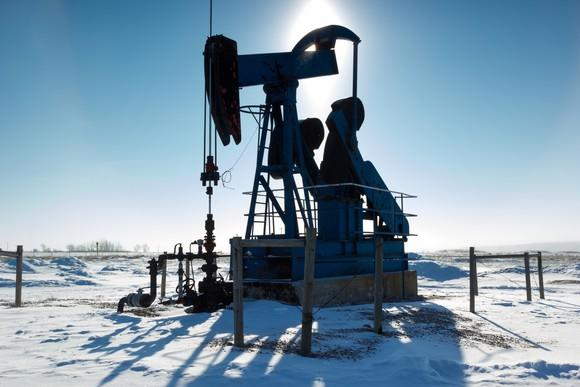 An oil pump with snow on the ground.