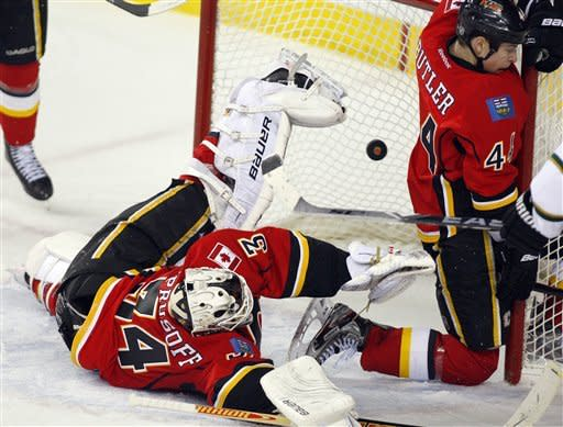 Calgary Flames goalie Miikka Kiprusoff, left, from Finland, and teammate Chris Butler try to stop a goal during second period NHL hockey action against the Dallas Stars in Calgary, Alberta, Monday, March 26, 2012. (AP Photo/The Canadian Press,/Jeff McIntosh)