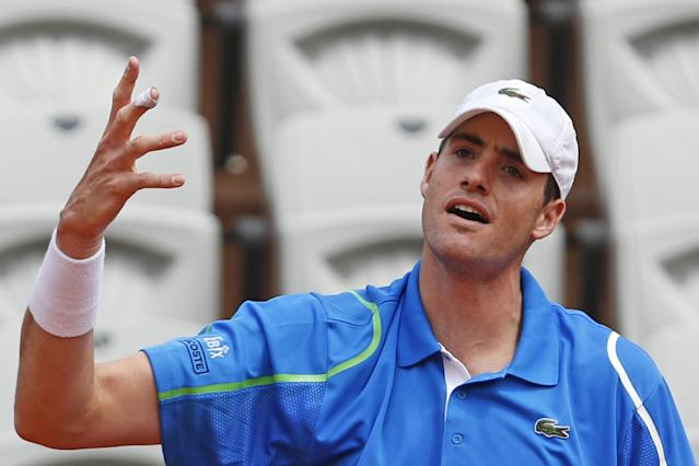John Isner of the U.S. misses a return during the fourth round match of the French Open tennis tournament against Tomas Berdych of the Czech Republic at the Roland Garros stadium, in Paris, France, Sunday, June 1, 2014. Berdych won in three sets 6-4, 6-4, 6-4. (AP Photo/Darko Vojinovic)