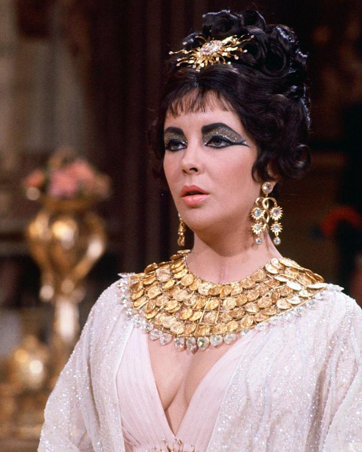 """<p>The industry has so much to thank <em>Cleopatra </em>for — from Liz & Dick to Taylor's iconic wardrobe throughout the blockbuster film. Joseff of Hollywood, the jeweler behind many of Hollywood's <a href=""""https://www.townandcountrymag.com/style/jewelry-and-watches/a13136532/elizabeth-taylor-cleopatra-jewelry/"""" rel=""""nofollow noopener"""" target=""""_blank"""" data-ylk=""""slk:biggest films at the time"""" class=""""link rapid-noclick-resp"""">biggest films at the time</a>, fitted the actress in pieces like this plated gold bib necklace, chandelier earrings, and hair piece.  </p>"""