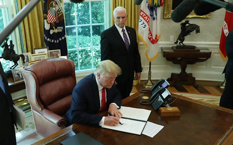 Donald Trump signs an executive order imposing new sanctions on Iran as Vice President Mike Pence (R) looks on - Getty Images North America