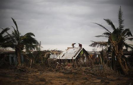 Fishermen and their family members repair the roof of their houses at the cyclone-hit Nalianuagaon village